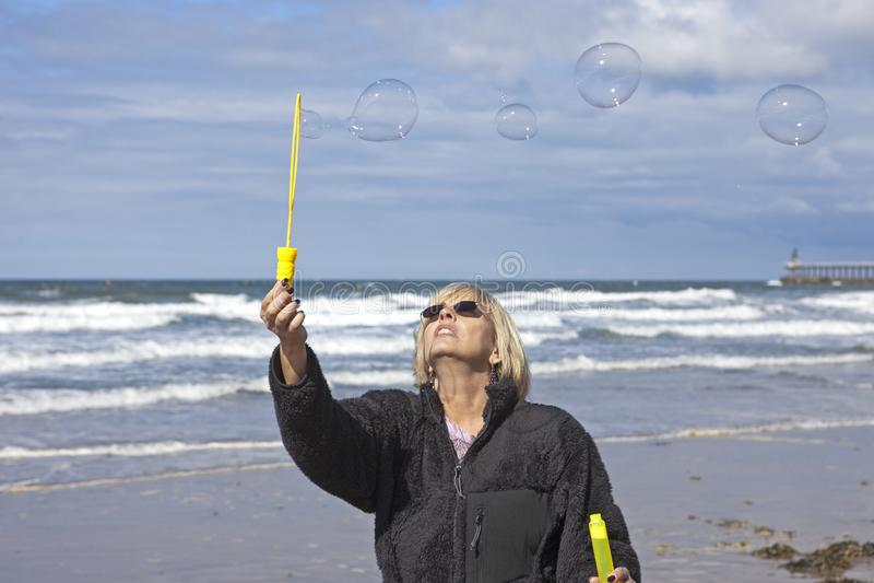 Burbujas de jabón de la muchacha que soplan en la playa fotos de archivo libres de regalías
