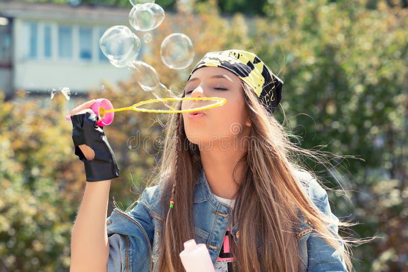 Burbujas de jabón de la mujer que soplan juguetona fotografía de archivo libre de regalías