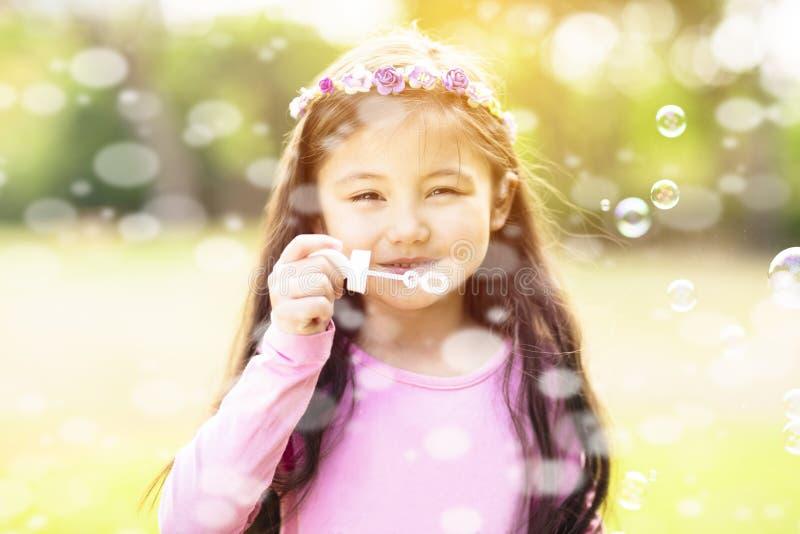 Burbujas de jabón de la niña que soplan fotos de archivo