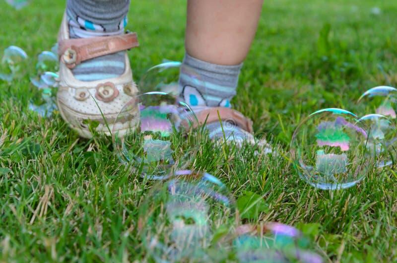 Burbujas de jabón y piernas del niño imagenes de archivo