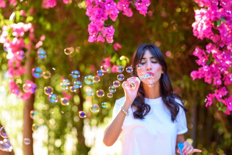 Burbujas de jab?n hermosas felices de la mujer que soplan joven al aire libre imagen de archivo libre de regalías