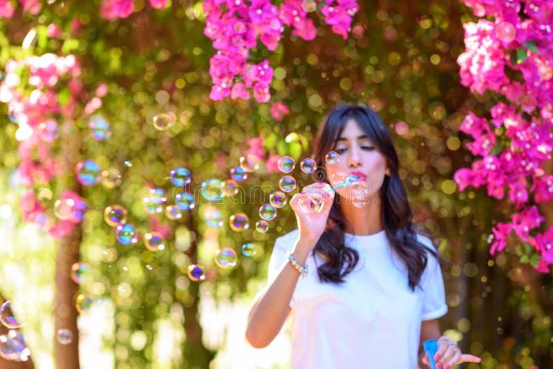 Burbujas de jab?n hermosas felices de la mujer que soplan joven al aire libre imagen de archivo
