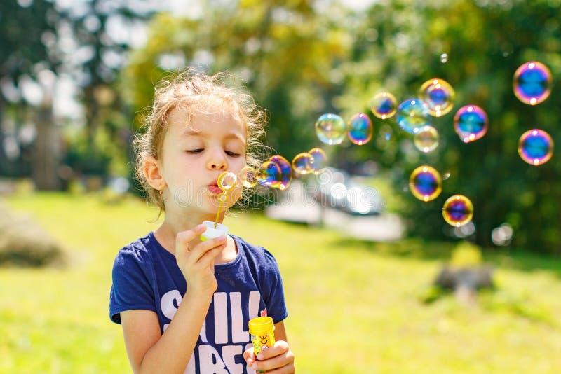 Burbujas de un jabón de la niña que soplan en parque del verano fotografía de archivo