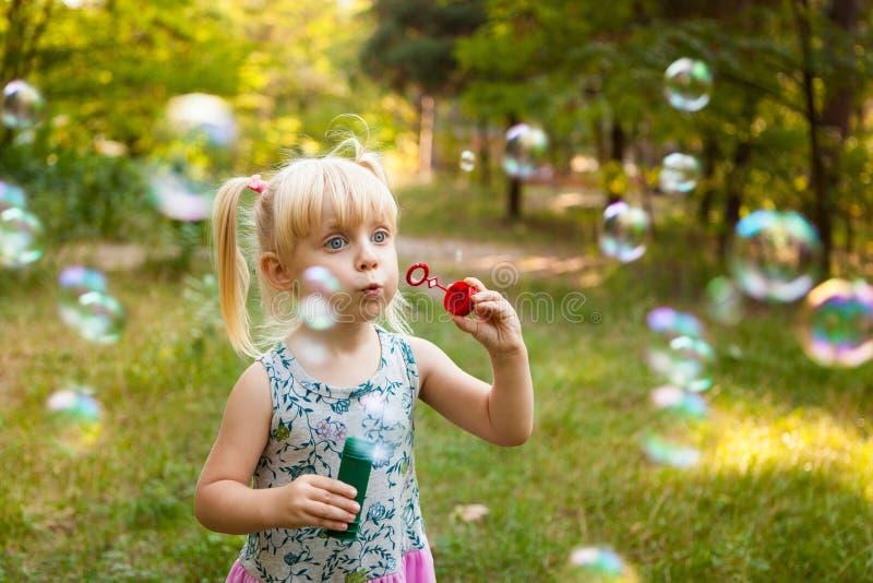 Burbujas del niño y de jabón en verano imagenes de archivo