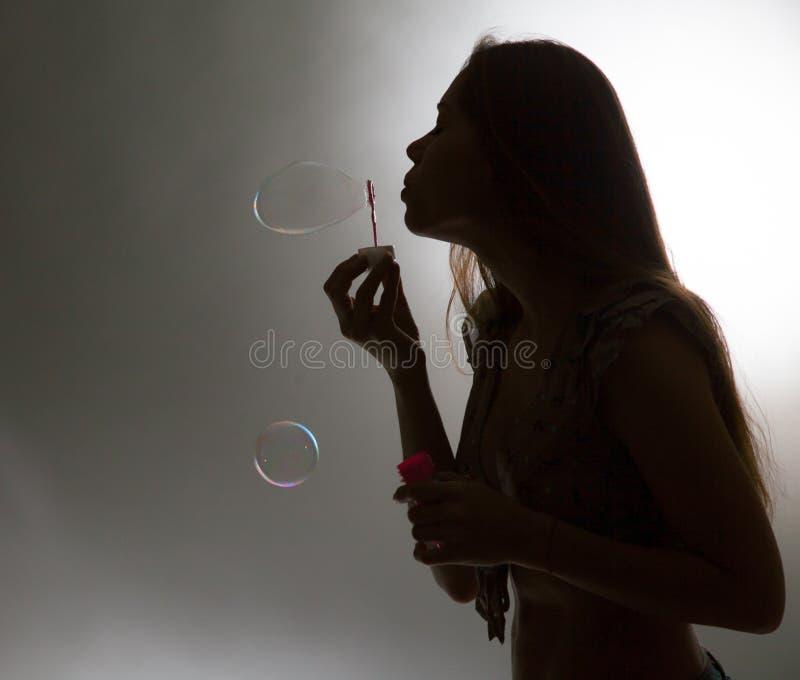 Burbujas del soplo de la muchacha fotos de archivo