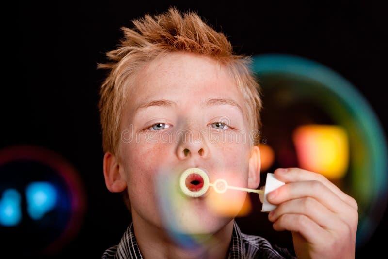 Burbujas grandes que vienen de la vara usada por el niño foto de archivo