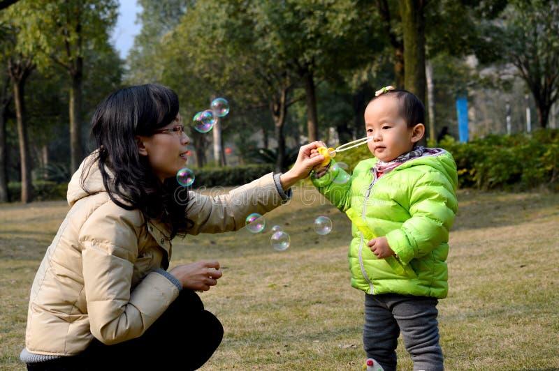 Burbujas que soplan de la madre y de la hija foto de archivo