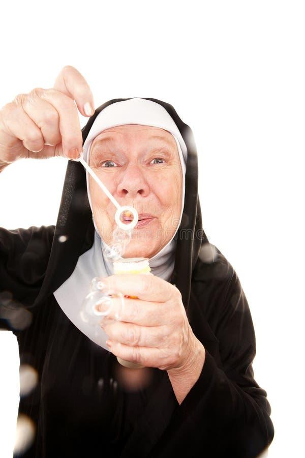 Burbujas que soplan de la monja divertida imagen de archivo libre de regalías