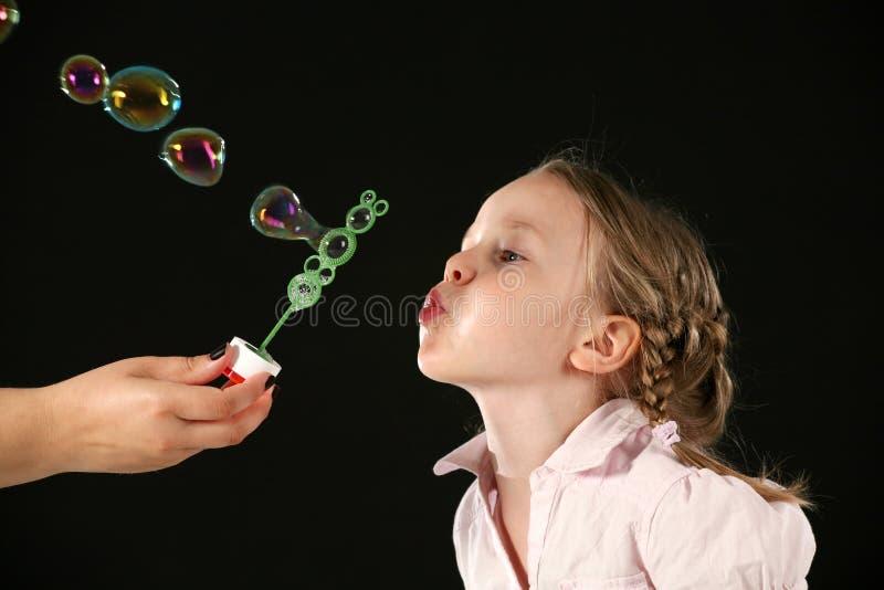 Burbujas que soplan de la muchacha imagenes de archivo