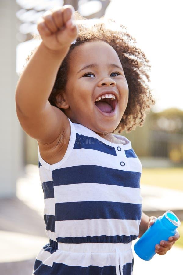 Burbujas que soplan de la muchacha negra joven fuera de su hogar fotografía de archivo libre de regalías