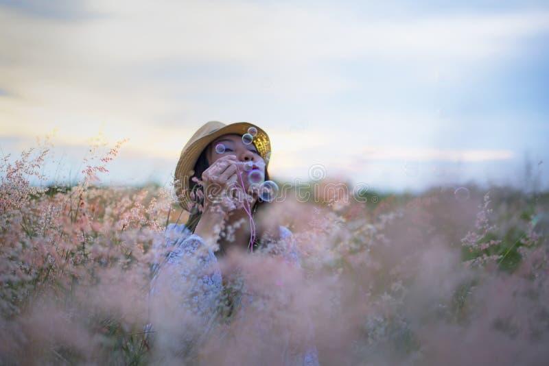 Burbujas que soplan de la mujer en prado imagenes de archivo