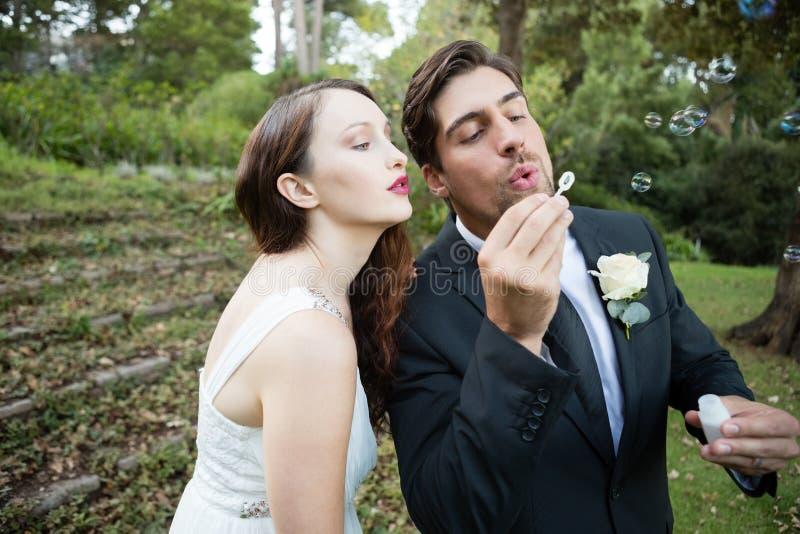 Burbujas que soplan de los pares del recién casado en parque fotos de archivo