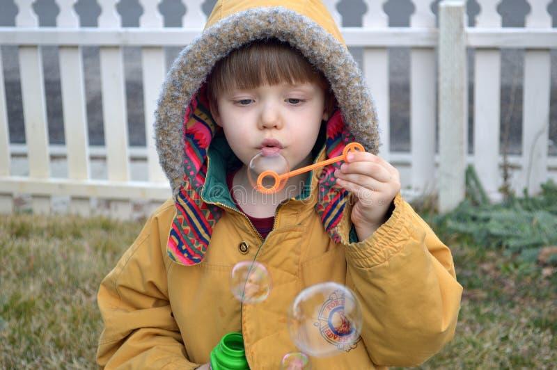Burbujas que soplan del muchacho en la yarda en invierno imagen de archivo libre de regalías
