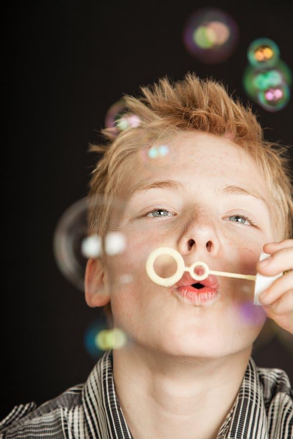 Burbujas que soplan del muchacho a través de la vara plástica fotografía de archivo libre de regalías