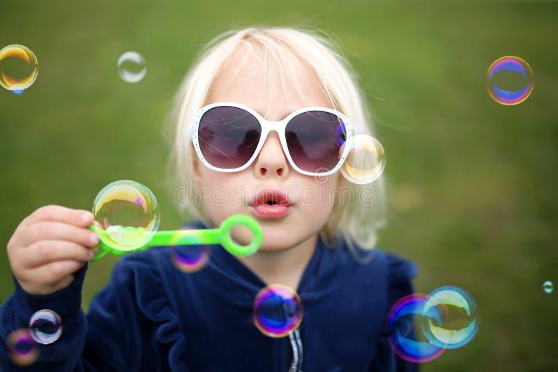 Burbujas que soplan del niño lindo de la niña afuera en un día de verano foto de archivo