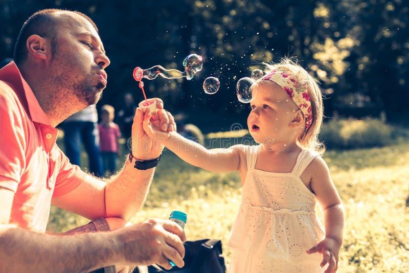 Burbujas que soplan del papá y de la hija fotos de archivo