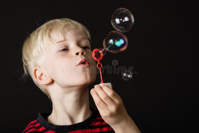 Burbujas que soplan del pequeño muchacho rubio atractivo fotos de archivo