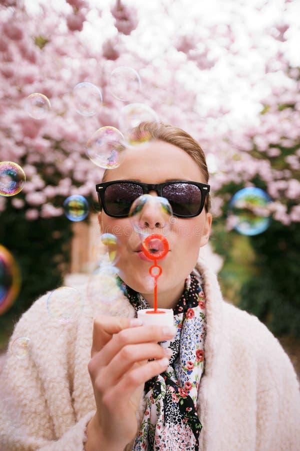 Burbujas que soplan femeninas jovenes lindas en el parque fotografía de archivo