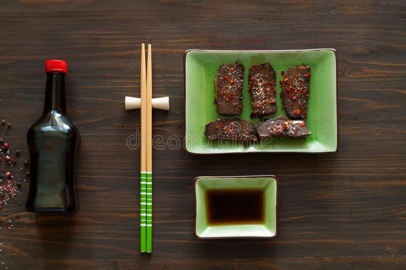 Burda, szybki smaży mięso w gorącym oleju na ceramicznym zieleń talerzu z chopsticks Wyśmienicie zrównoważony karmowy pojęcie, ko fotografia stock