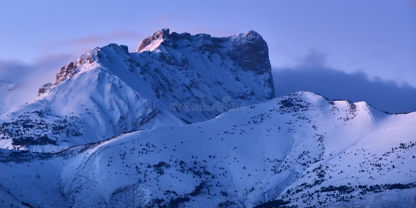 Bure Peak Pic de Bure in the Devoluy Mountain range at dusk in Winter. Hautes-Alpes, Alps, France. Bure Peak Pic de Bure in the Devoluy Mountain range at dusk in stock photography
