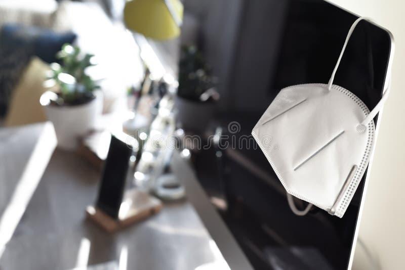 Bureau à domicile avec masque facial représentant le travail à domicile pendant la période d'isolement et de distanciation social image stock