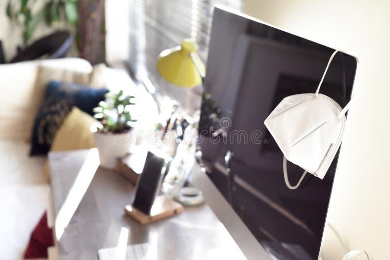 Bureau à domicile avec masque facial représentant le travail à domicile pendant la période d'isolement et de distanciation social photos stock