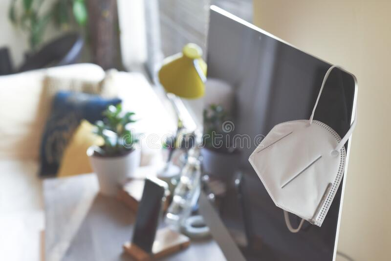 Bureau à domicile avec masque facial représentant le travail à domicile pendant la période d'isolement et de distanciation social image libre de droits