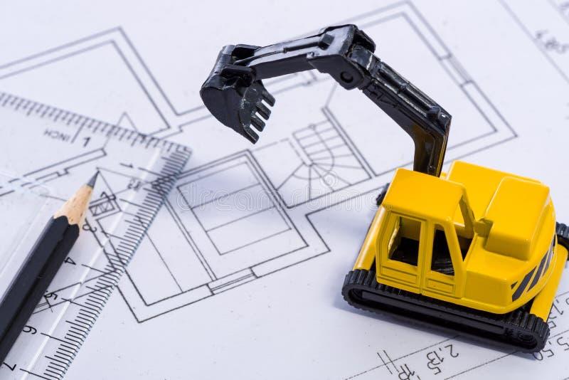 Bureau avec excavatrice, règle et crayon de jaune de modèle la mini photographie stock libre de droits