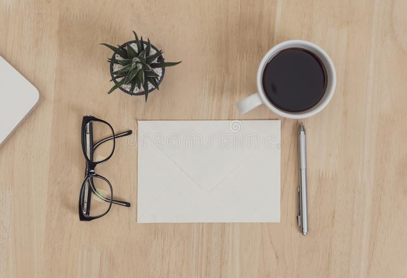 Bureau avec l'enveloppe de papier blanc et la tasse de café Table de vue supérieure de ci-dessus avec l'espace de copie pour l'en photographie stock
