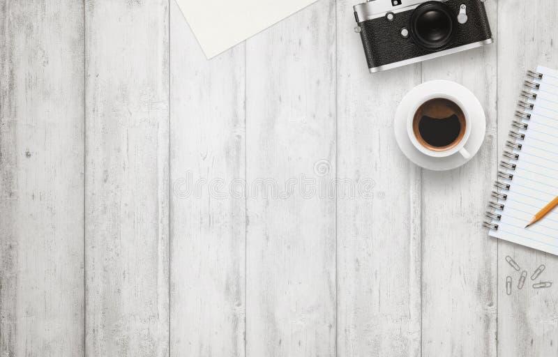 Bureau avec l'espace libre pour le texte Appareil-photo, tasse de café, papier, bloc-notes, crayon sur la table en bois blanche photo libre de droits