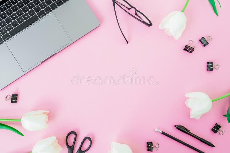 Bureau avec l'ordinateur portable, les tulipes blanches, les verres, le stylo et les ciseaux sur le fond rose Configuration plate image libre de droits