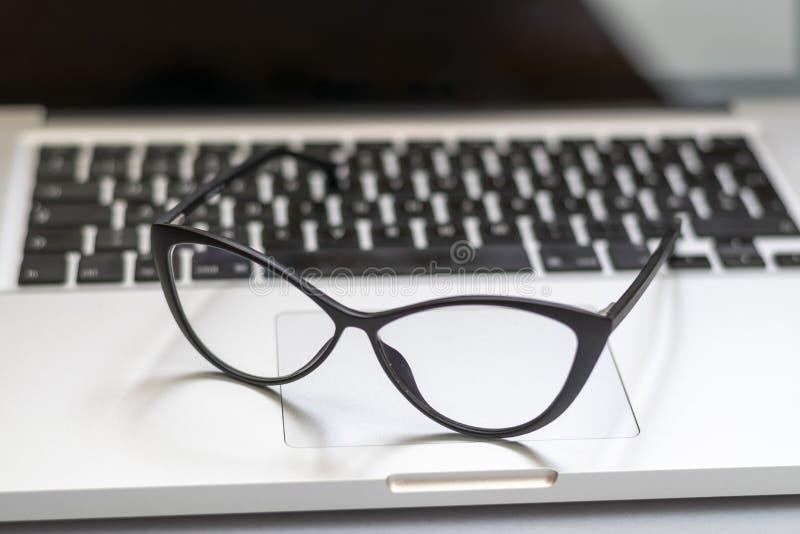 Bureau avec l'ordinateur portable, les verres et d'autres articles photographie stock