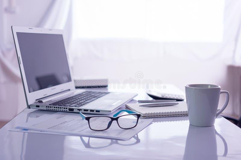 Bureau avec l'ordinateur portable sur le bureau blanc photographie stock libre de droits