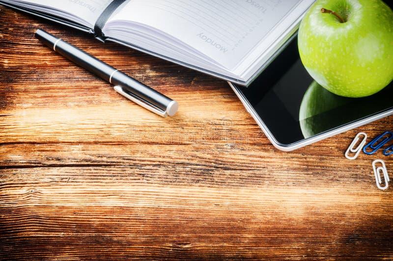 Bureau avec l'ordre du jour de papier, le comprimé numérique et la pomme verte images libres de droits