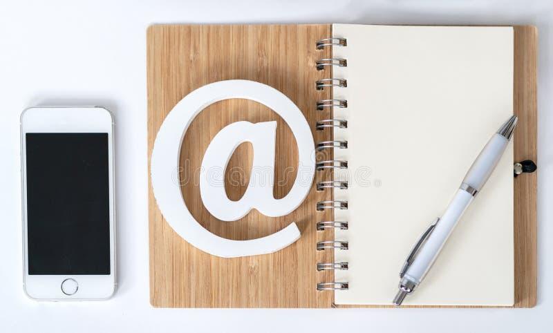 Bureau avec le bloc-notes et les verres et le symbole d'email Vue sup?rieure photo stock