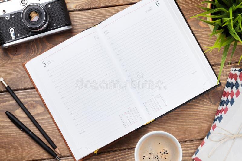 Bureau avec le bloc-notes, l'appareil-photo, les approvisionnements et la fleur de calendrier images libres de droits