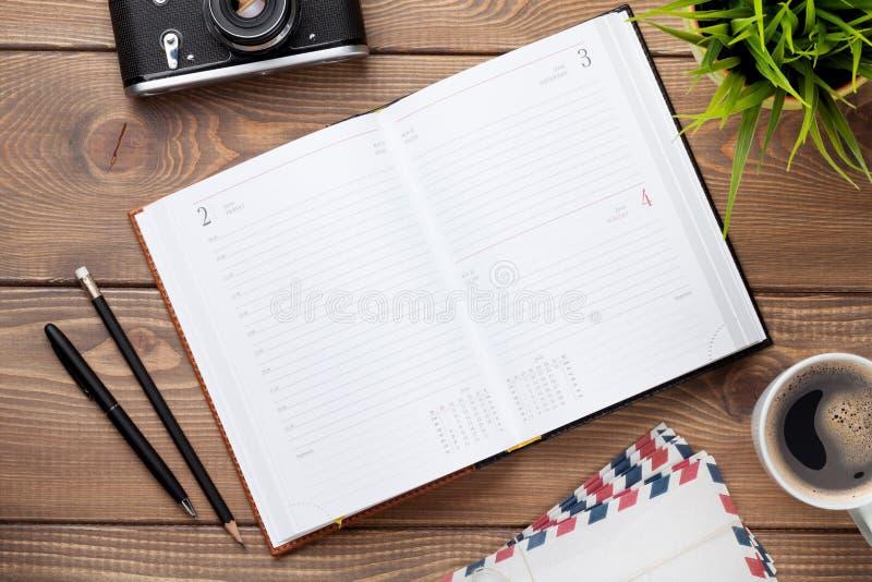 Bureau avec le bloc-notes, l'appareil-photo, les approvisionnements et la fleur de calendrier photos stock