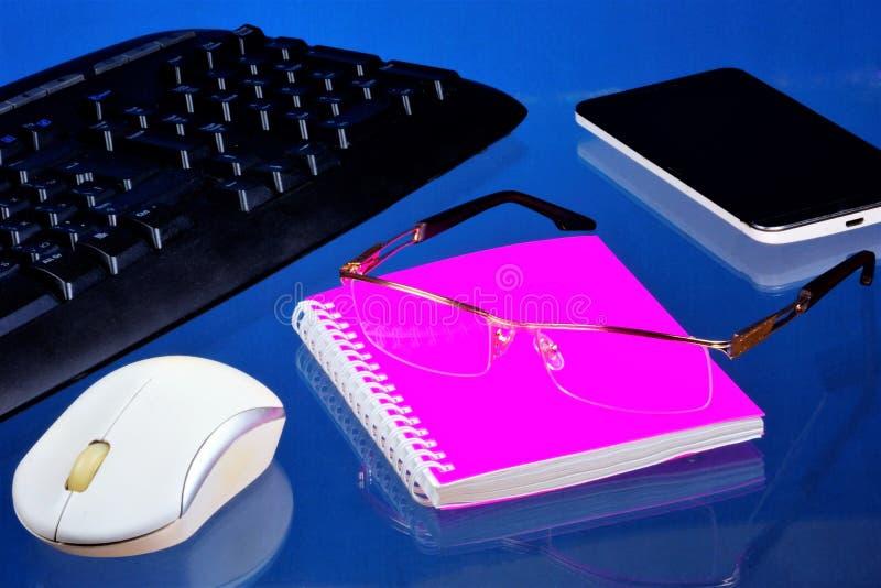 Bureau avec les accessoires nécessaires, fond bleu Sur le carnet de bureau de bureau pour les disques importants, smartphone photographie stock