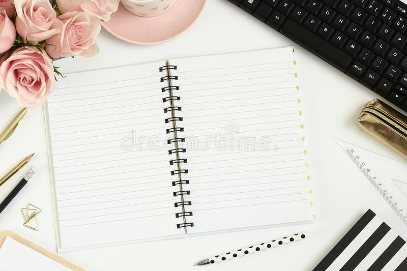 Bureau avec les fleurs roses, le carnet vide et l'ordinateur photos stock