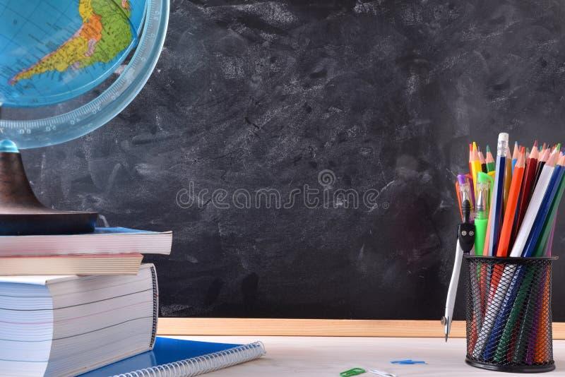 Bureau avec les outils et le tableau noir d'école images libres de droits