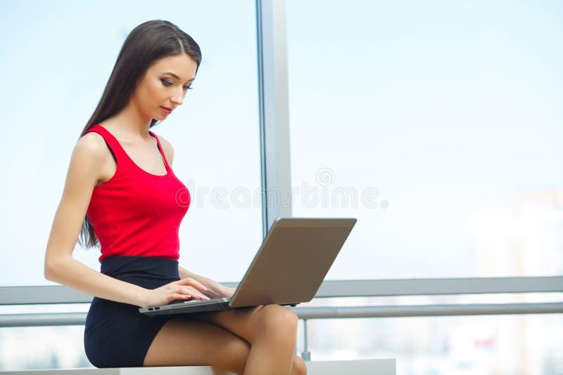 bureau Bedrijfsvrouw die zich bij het Grote Venster bevinden Licht Modern Bureau Gekleed in Rode Sweater en Zwarte Rok Versiering stock foto's