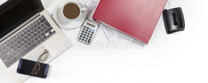 Bureau blanc avec l'ordinateur portable, dossier, calculatrice, café, verre photo libre de droits