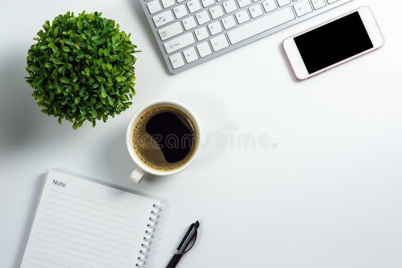 Bureau blanc avec le smartphone noir d'écran vide, la tasse de café, le carnet vide, le stylo, le clavier d'ordinateur et le pot  images stock