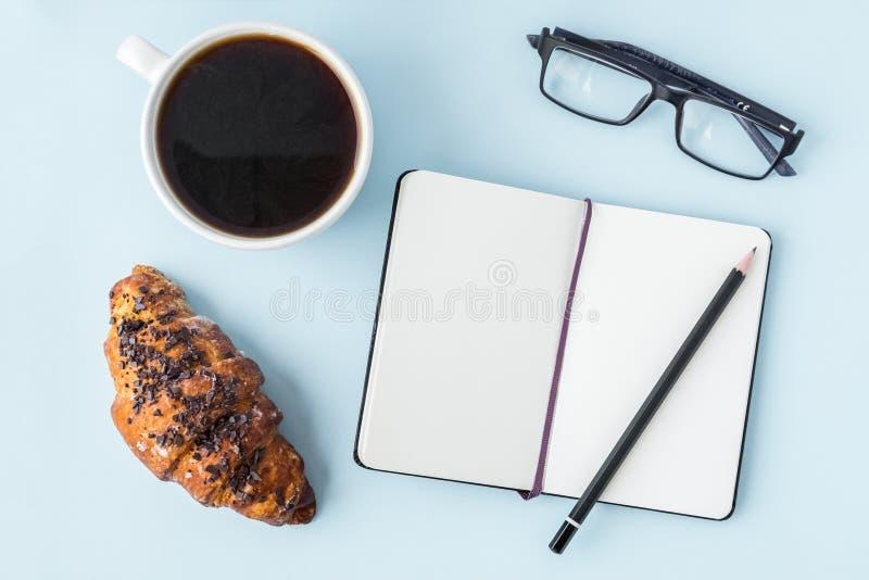 Bureau blauwe lijst met lege blocnote, potlood, glazen, verse croissant en koffiekop Exemplaarruimte voor tekst Vlak leg stock foto
