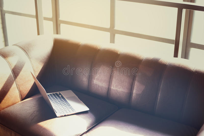 Bureau coworking ensoleillé moderne de grenier, ordinateur portable ouvert sur un sofa en cuir, lumière du soleil par une fenêtre photographie stock