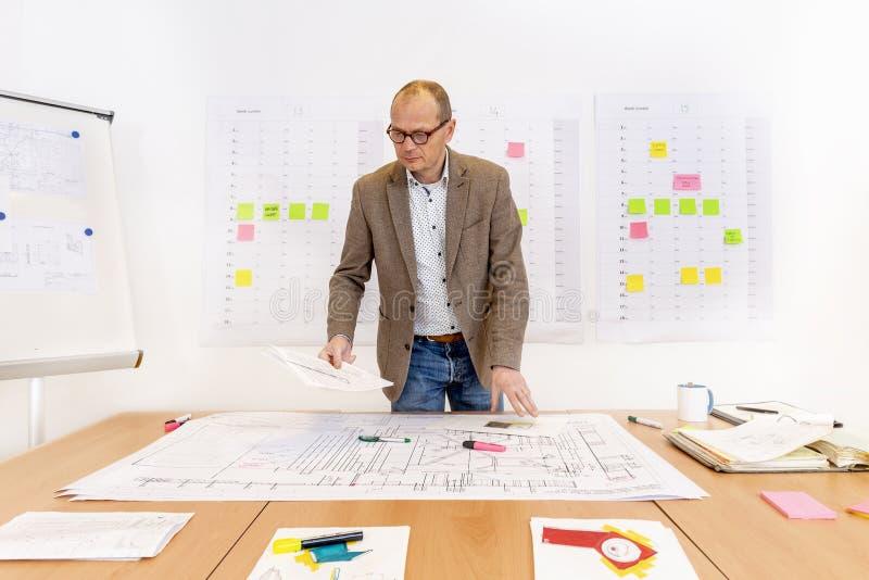 Bureau d'entrepreneur avec la planification et les dessins techniques photographie stock