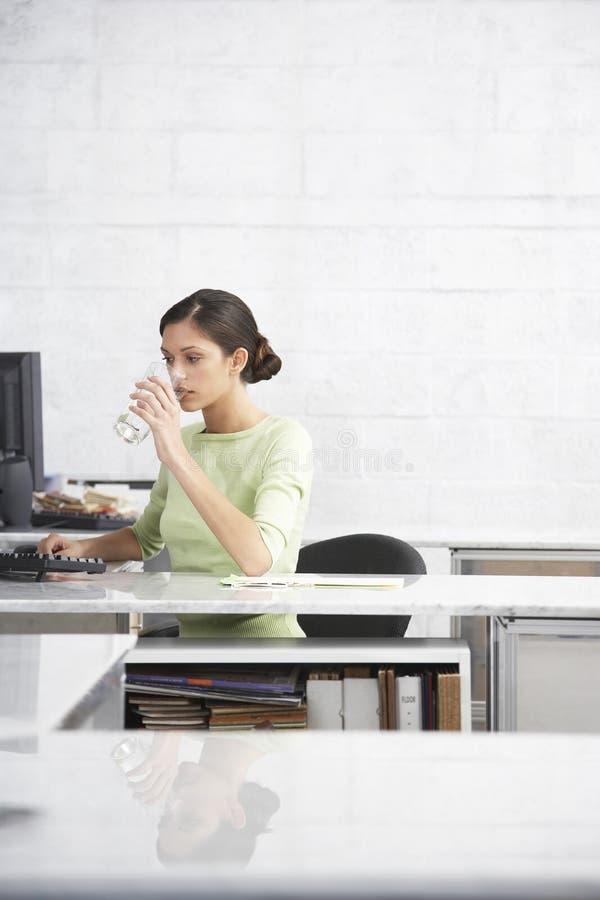 Bureau d'ordinateur de Drinking Water At de femme d'affaires images libres de droits