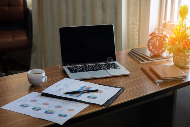 Bureau d'ordinateur de gestion avec l'ordinateur portable de bureau, le carnet, l'horloge, le stylo et le compte rendu annuel et  image libre de droits