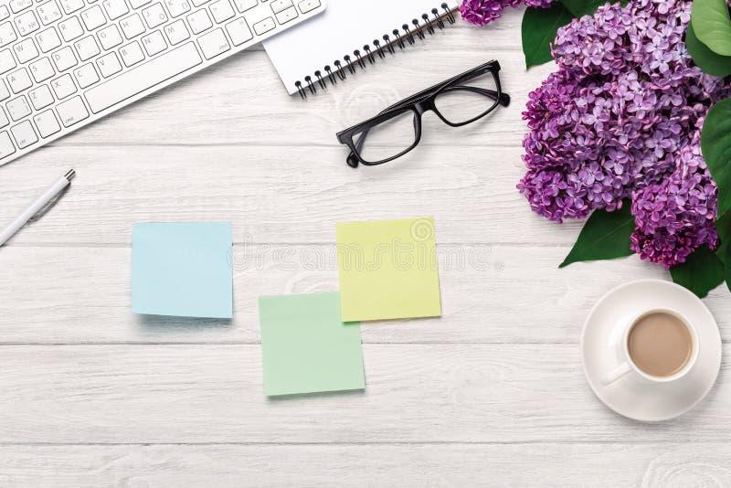 Bureau de bureau avec un bouquet des lilas, de la tasse de café, du clavier, du carnet et des autocollants colorés sur les consei images libres de droits