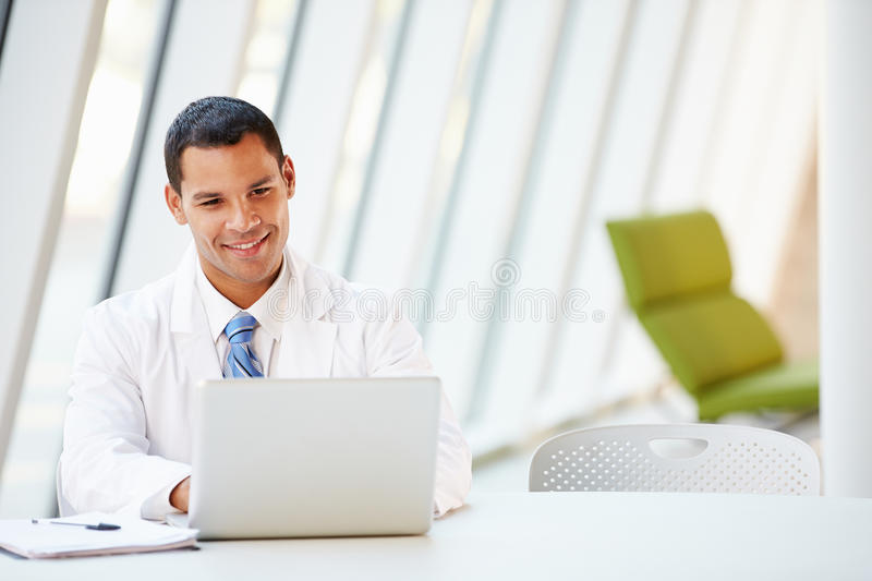 Bureau de docteur Using Laptop Sitting At dans l'hôpital moderne photos stock